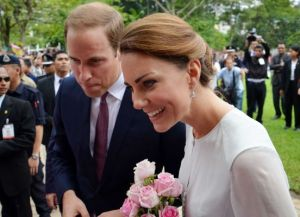 Britain's Prince William and his wife Kate smile to the public during a walk through a central city park in Kuala Lumpur, Malaysia.